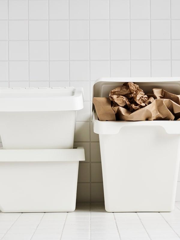 Tiga tong sampah SORTERA berwarna putih, salah satunya penuh dengan kertas berwarna coklat, terletak di ruang berjubin berwarna putih.