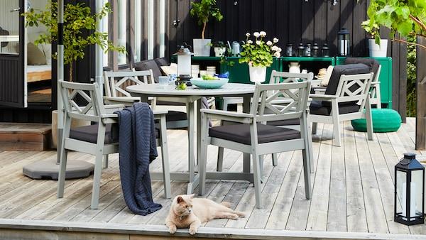 Tilava terassi, jossa harmaat BONDHOLMEN-puutarhakalusteet, kasveja, lyhty, sininen viltti ja lattialla makaava kissa.