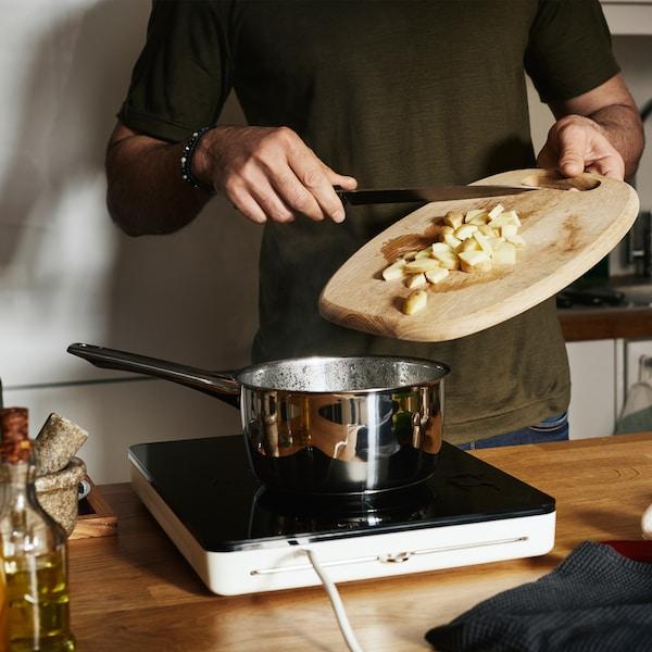 도마 위의 자른 감자를 TILLREDA 틸레다 휴대용 인덕션레인지 위의 크롬 캐서롤에 넣고 있어요.