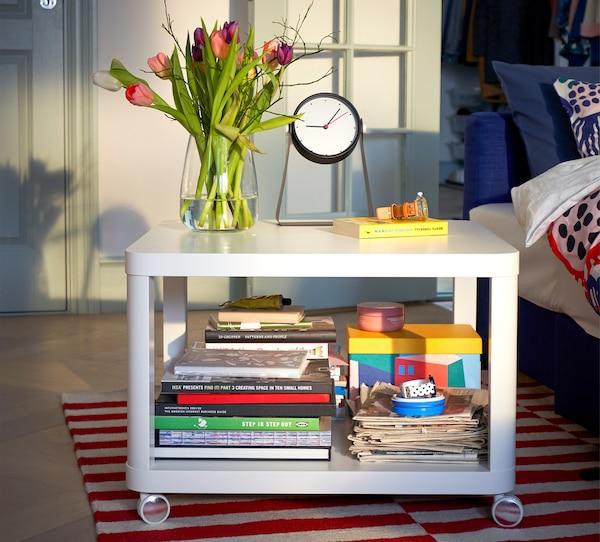 TINGBY طاولة جانبية بيضاء على عجلات، مع الكثير من الكتب في المستوى السفلي ومع مزهرية وزهور وساعة في الأعلى.
