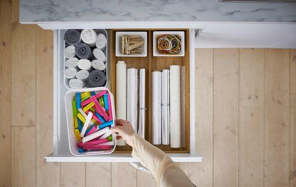 Tiroir de cuisine ouvert et contenant des accessoires de rangement
