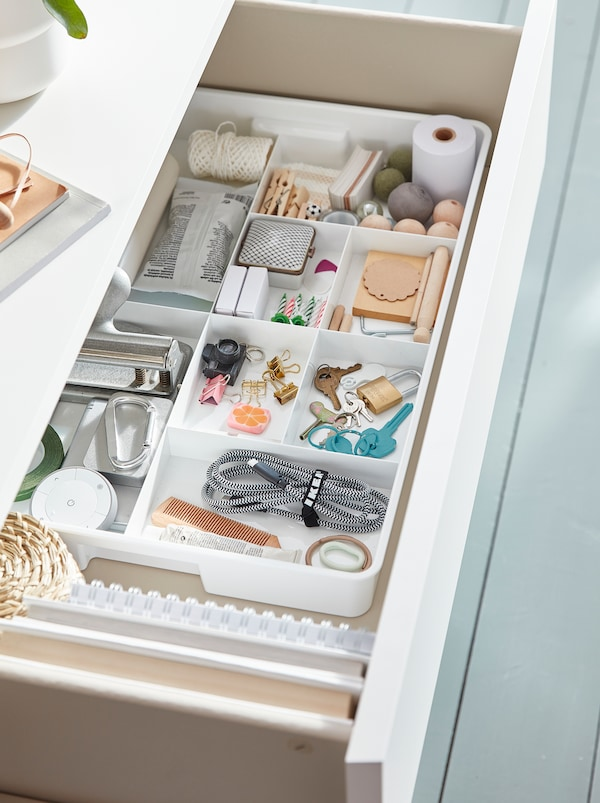 Tiroir ouvert rempli de boîtes de rangement blanches KUGGIS avec huit compartiments remplis de clés, de pinces, de fils et de fournitures de bureau.