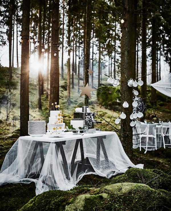 Tisch mit Hochzeitstorte und weißen Tellern, u. a. mit ODDVALD Tischböcken in Schwarz