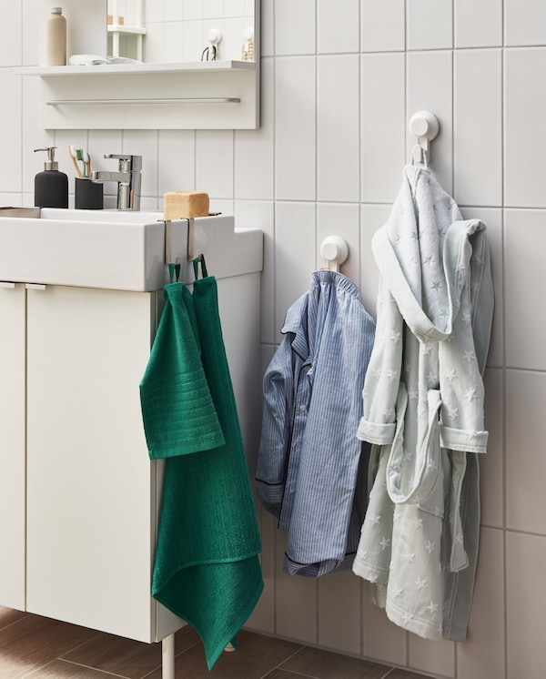 TISKEN kuke s vakuumskim držačima na pločastom zidu pored umivaonika. Dečja pidžama i bade mantil su ovde okačeni.