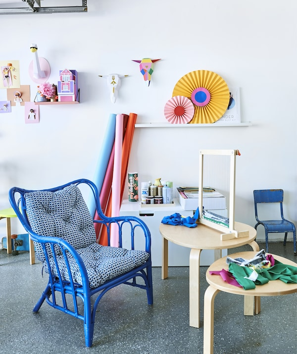 Tkalački stan i tkanina na dva drvena pomoćna stola, plava fotelja i šarene umjetnine na bijelom zidu.