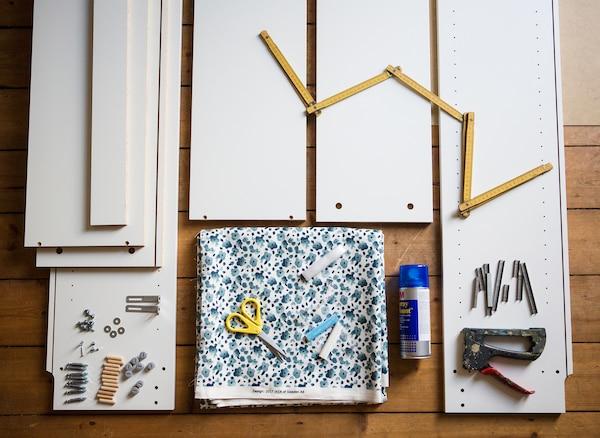 Tkanina, fragment regału i narzędzia ułożone na podłodze.