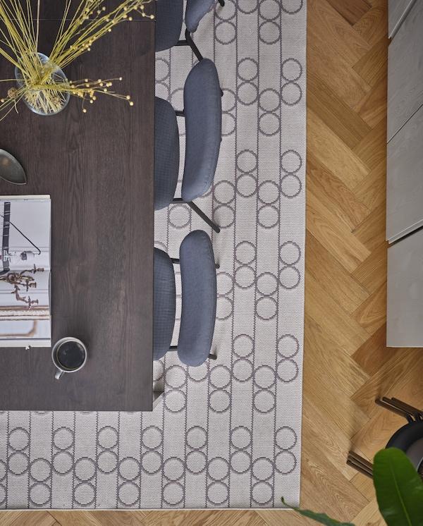 Tkany na płasko dywan w geometryczne, koliste wzory ułożony pod ciemnobrązowym stołem jadalnianym i szarymi krzesłami.