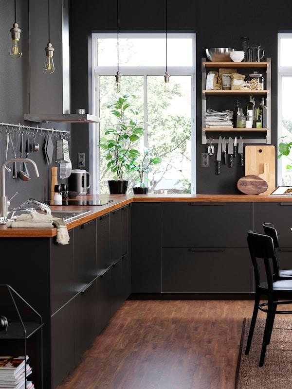 Tmavá a útulná kuchyně s černými skříňkami a zásuvkami.