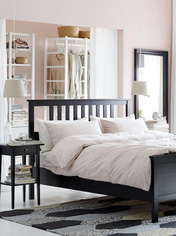 Tmavá drevená posteľ s bielym posteľným povlečením, skrinka so zrkadlom.