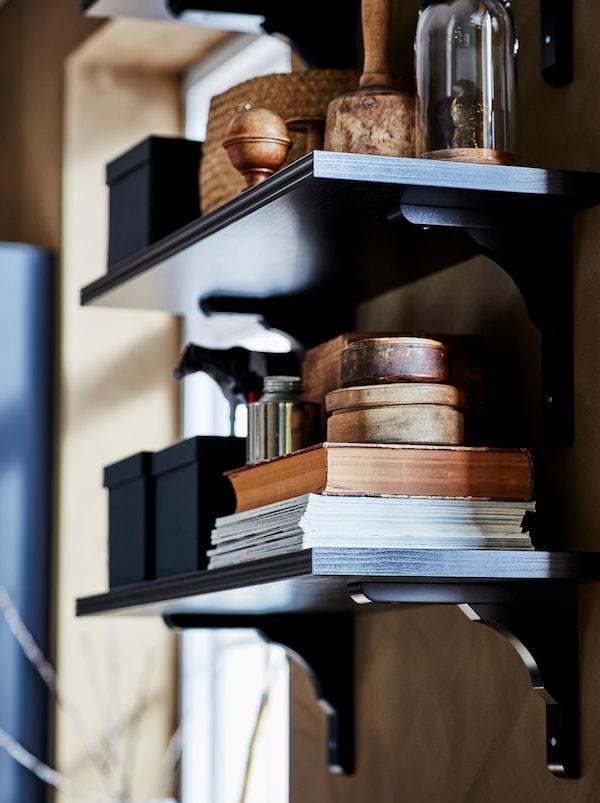 Tmavá nástenná polica BERGSHULT/RAMSHULT s časopismi a knihami, škatuľami a inými doplnkami.