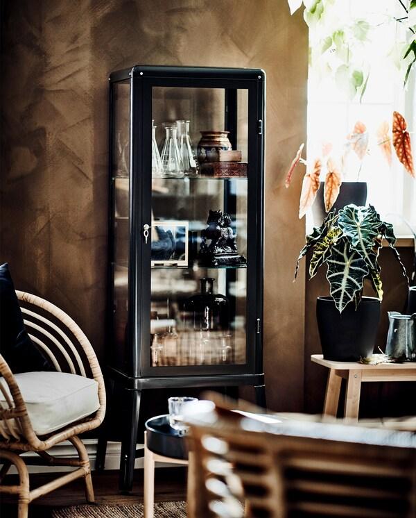 Tmavě šedá vitrina s dekoracemi uvnitř, vedle je ratanové křeslo  s polštářem