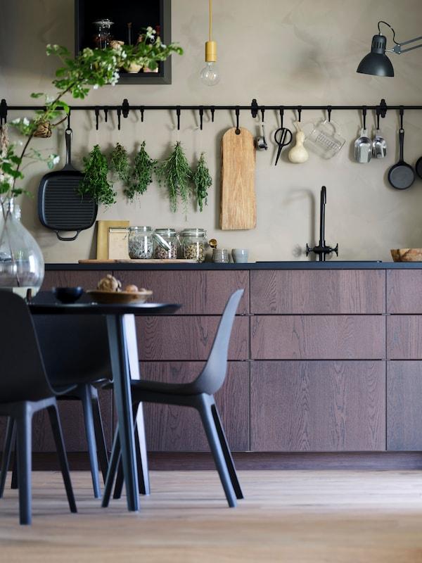 Tmavohnedá kuchyňa s čiernou pracovnou doskou a čiernym drezom. Nad ňou je čierny závesný úložný systém HULTARP na béžovej stene. V popredí čierny stôl a čiernomodré stoličky BALTSAR.