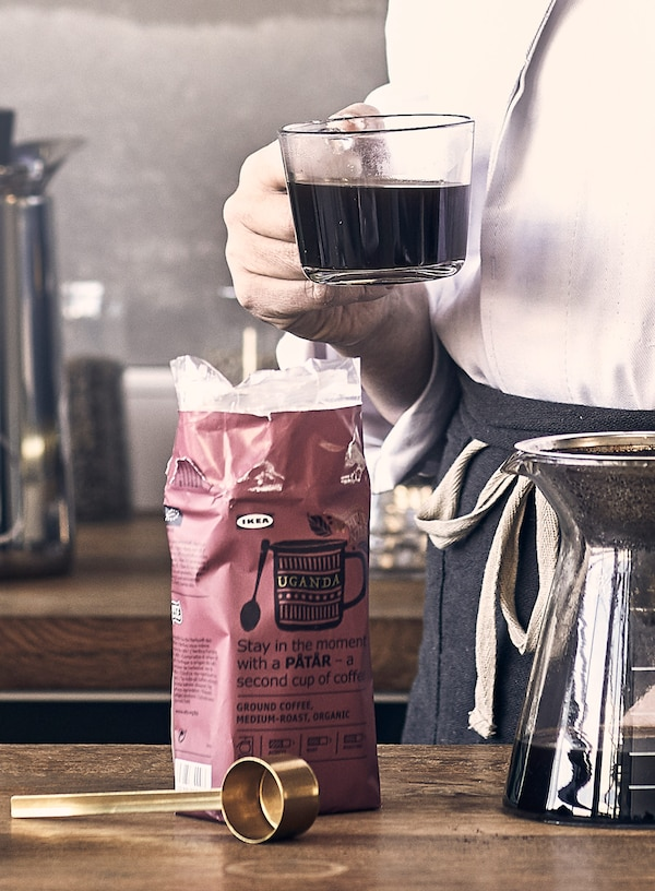 Tmavoružové balenie kávy IKEA PÅTÅR, vybavenie na prípravu kávy a osoba, ktorá drží šálku kávy.