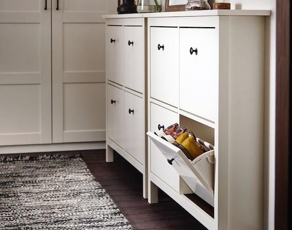 To hvide skoskabe med hver fire rum, der står ved siden af hinanden. Et af rummene er åbent, så man kan se sko inden i.