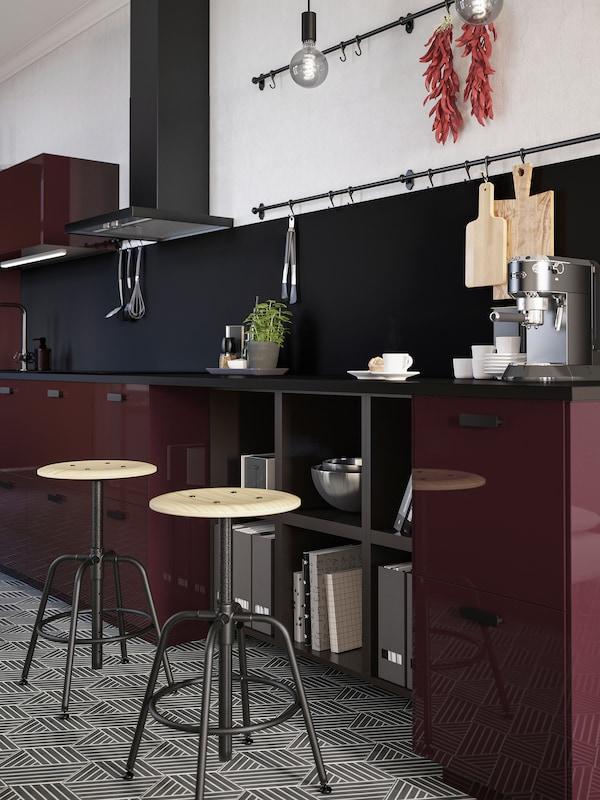 To krakker i furu og svart står ved en kjøkkenbenk i et mørk rødbrunt kjøkken. På benkeplata står det en kaffemaskin og kaffekopper.