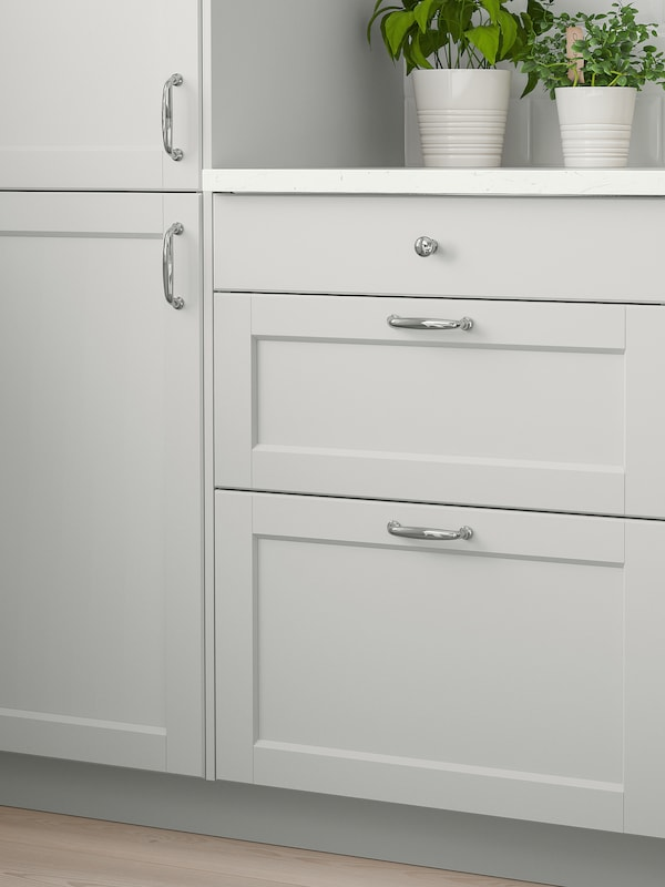 To lysegrå kjøkkenskap med lysegrå dører, hvit benkeplate med to potteplanter på og lysegrå skuffefronter under.