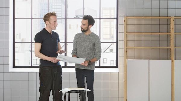 To mænd står og taler i et tomt rum med flisebelagte vægge.