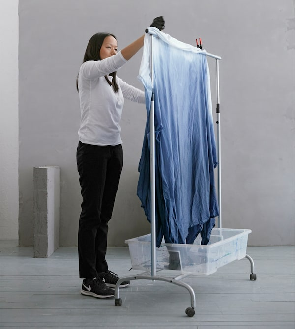 To make unique bedding for your dorm, you can dye cotton fabric like BOMULL from IKEA. We used a clothes rack as a drying rack with a plastic bin underneath to catch drips.