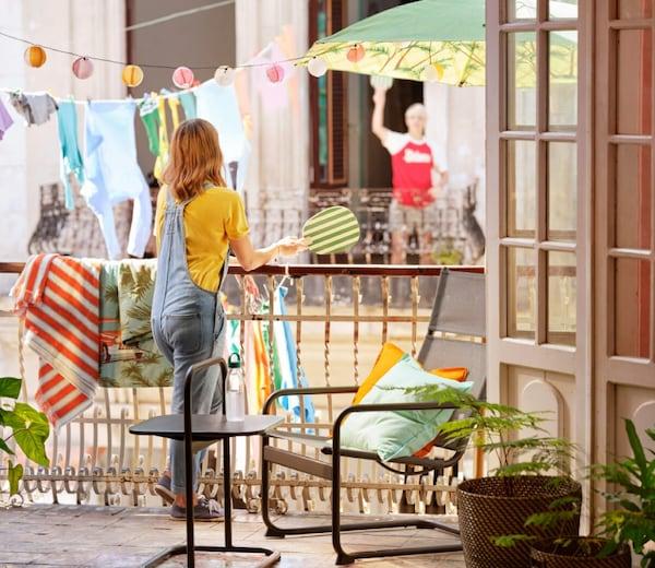 To mennesker spiller ping-pong fra hver sin altan omgivet af farverige tekstiler