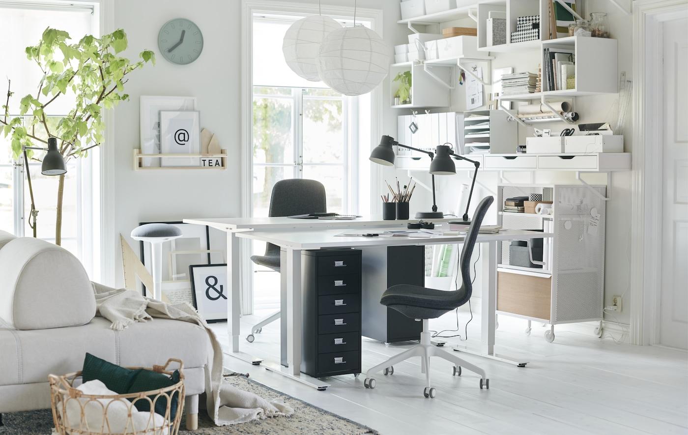 To skrivebord og arbeidsstoler i hjørnet i ei hvit stue med veggoppbevaring.