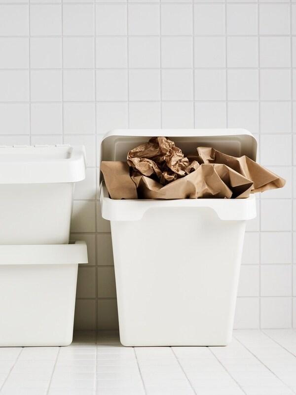To små og en stor SORTERA affaldsspande, der bruges til at affaldssortere i, står i et rum med hvide fliser.