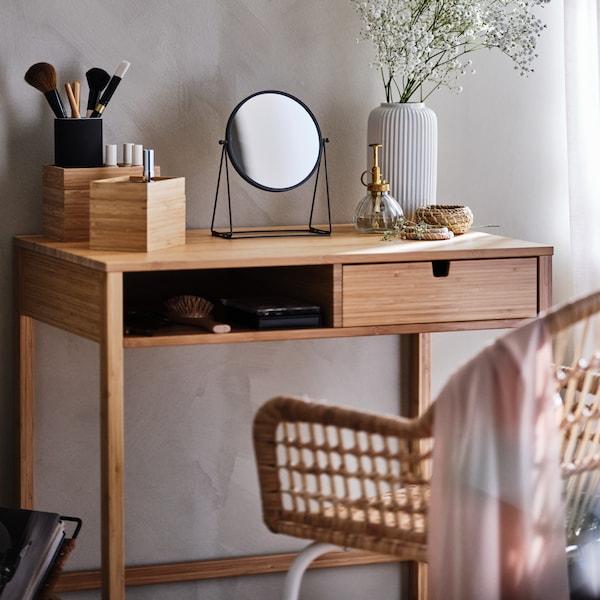 Toaletní stolek v ložnici se zrcadlem, vázou a kosmetickými štětci.