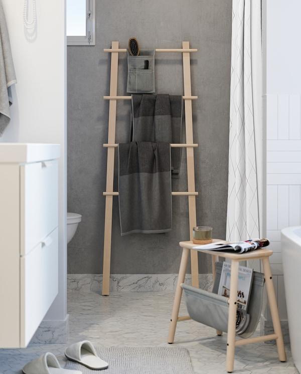 Toalhas cinzentas penduradas num toalheiro VILTO em bétula, entre uma sanita e um chuveiro – adapta-se perfeitamente a espaços pequenos.