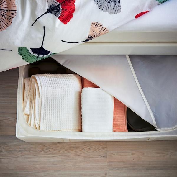 Toalhas guardadas numa caixa de arrumação com fecho debaixo da cama com roupa de cama com padrão floral.