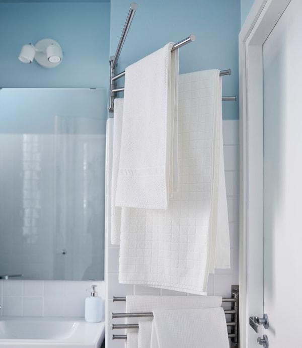 Toallas blancas colgadas de un toallero que se pliega hacia la pared en este pequeño baño.