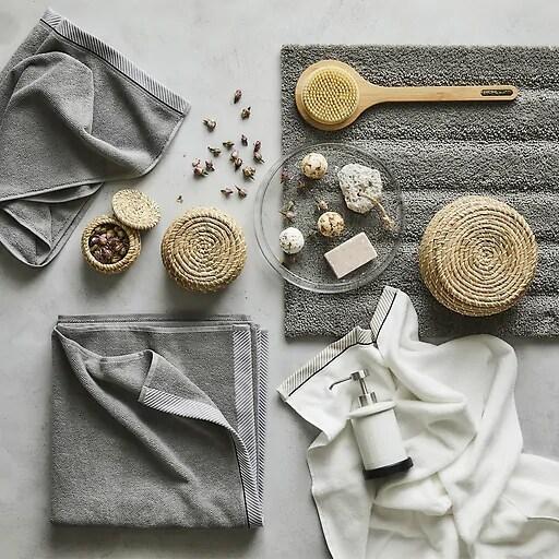 Toallas grises y accesorios de baño dispuestos sobre una superficie gris.