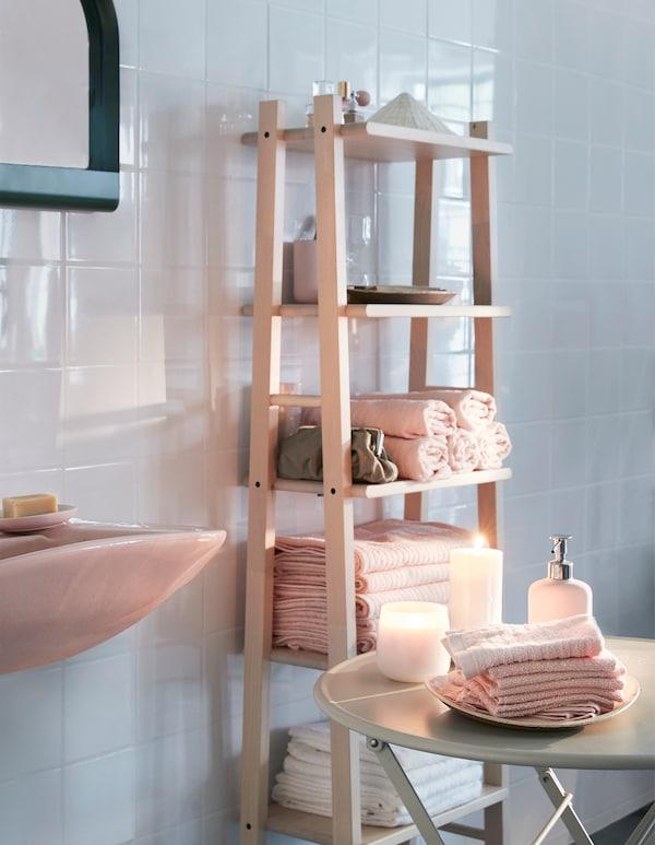 Toallas VÅGSJÖN en rosa pálido apiladas y enrolladas en una estantería abierta, cerca de una mesa con velas y toallas rosas para la cara.