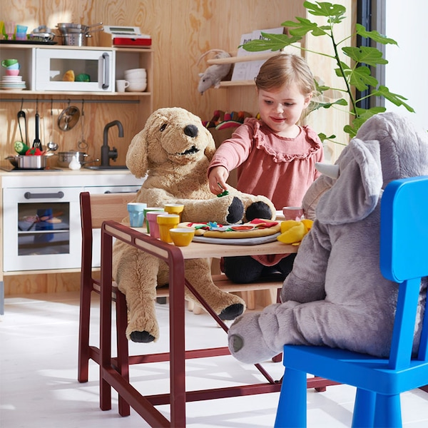 Toddler plays with her cuddles at the YPPERLIG children's table | IKEA