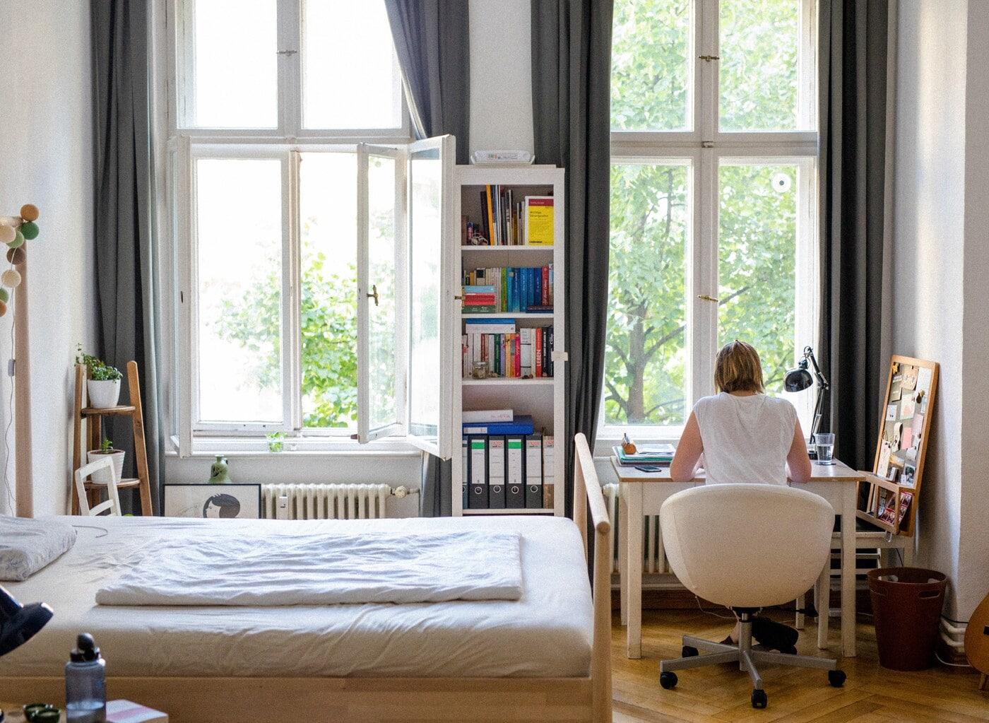 書棚とデスクがある小さな明るいベッドルーム。デスクの前には若い女性がカメラに背を向けて座っています。