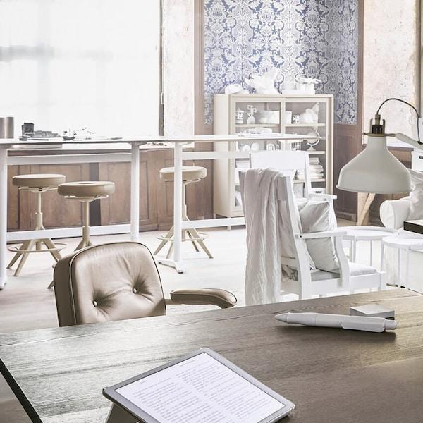 Toimiston työtila, jossa on erilaisia pöytiä ja istuimia, pöytävalaisimet, lattiavalaisin sekä avoimet ja suljetut säilytysyksiköt.