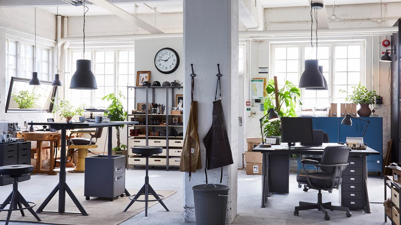 Toimistotila, jossa on säädettäviä jakkaroita, istuma- ja seisomapöytiä, säilytystilaa, kattovalaisimia, monenlaisia esineitä ja viherkasveja.