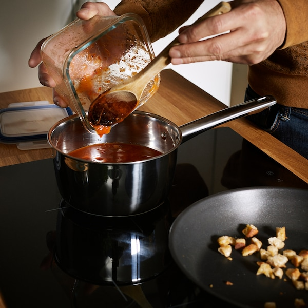 Tomato sauce being poured from an IKEA 365+ food container into a saucepan placed on an induction hob.
