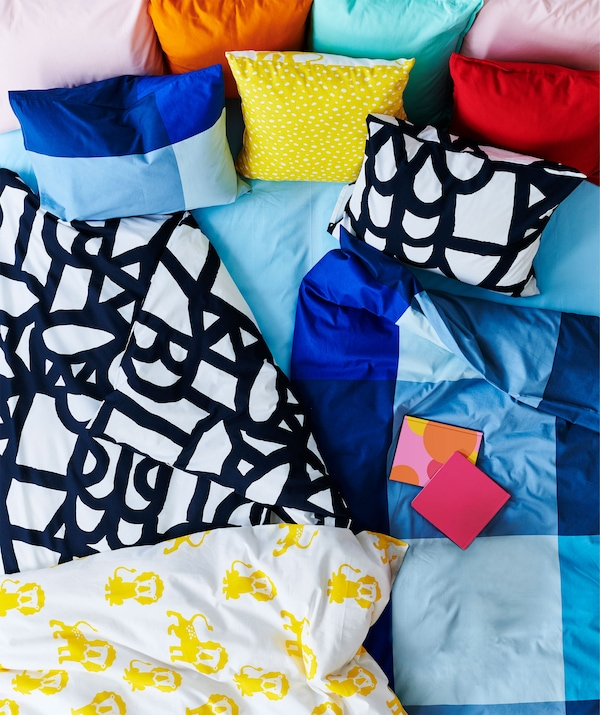Top of a bed covered with a rich mix of sharply coloured and patterned duvets, cushions and textiles.