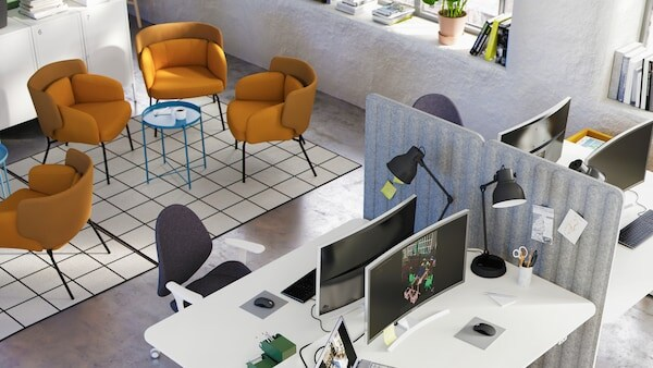 Top view of four wood color top sit stand desks at various heights with white desk chairs and orange soft seating chairs.