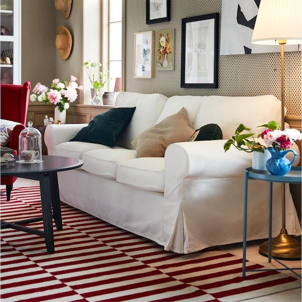 トラディショナルな雰囲気のリビングルーム。レッドとホワイトのラグの上に置かれたホワイトのEKTORP/エークトルプ 3人掛けソファ。