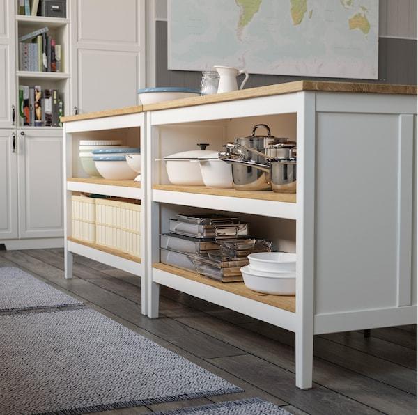 TORNVIKEN جزيرة المطبخ ذات اللون الأبيض من ايكيا تحتوي على أرفف داخلية تقليدية من الخشب الخفيف. يتوفر في أحد الجانبين مساحة تخزين للأواني، أما الآخر فهو مخصص للجلوس.