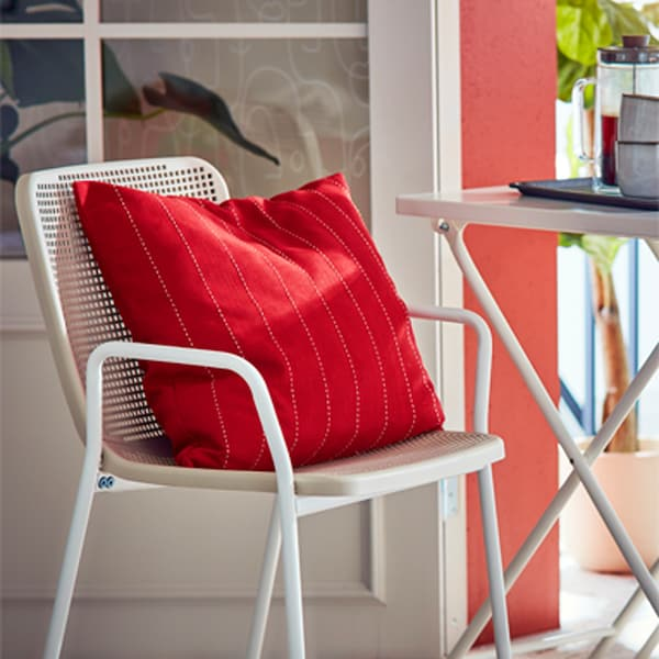 TORPARÖ indoor/outdoor furniture in a balcony setting together with red FESTHOLMEN cushions and GLADELIG mugs.