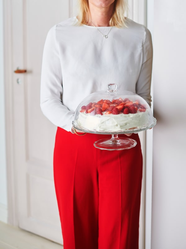 Torso and legs of a party-dressed woman holding an ARV BRÖLLOP glass serving stand with lid containing a strawberry cake.