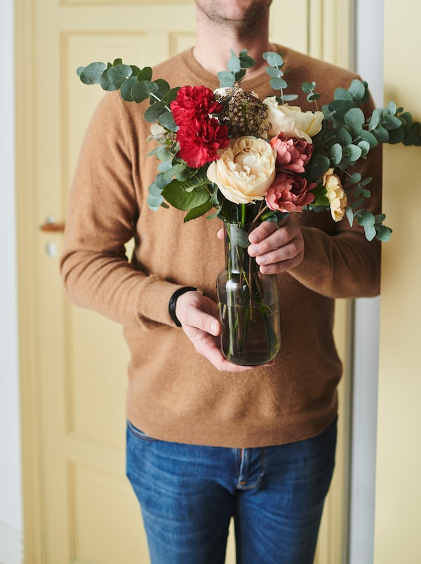 Torso of a man in jeans and sweater holding a FÖRENLIG vase filled with a bouquet including SMYCKA artificial flowers.