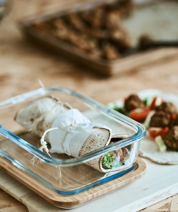 Tortilja smotana i zavezana u staklenoj posudi pokraj otvorene tortilje sa sastojcima za punjenje.