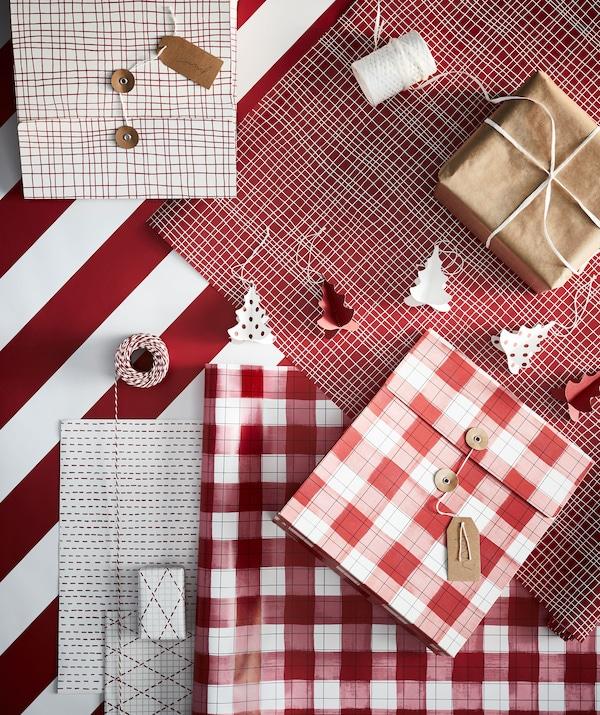 Tout le nécessaire pour emballage en place: papier de différentes couleurs et motifs, ficelle, ciseaux, étiquettes et cadeaux emballés.