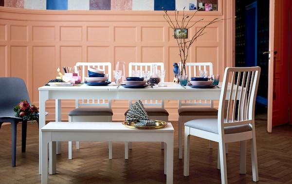 طقم طاولة طعام بيضاء طويلة، وكراسي ومقعد مع أدوات مائدة بألوان زاهية.