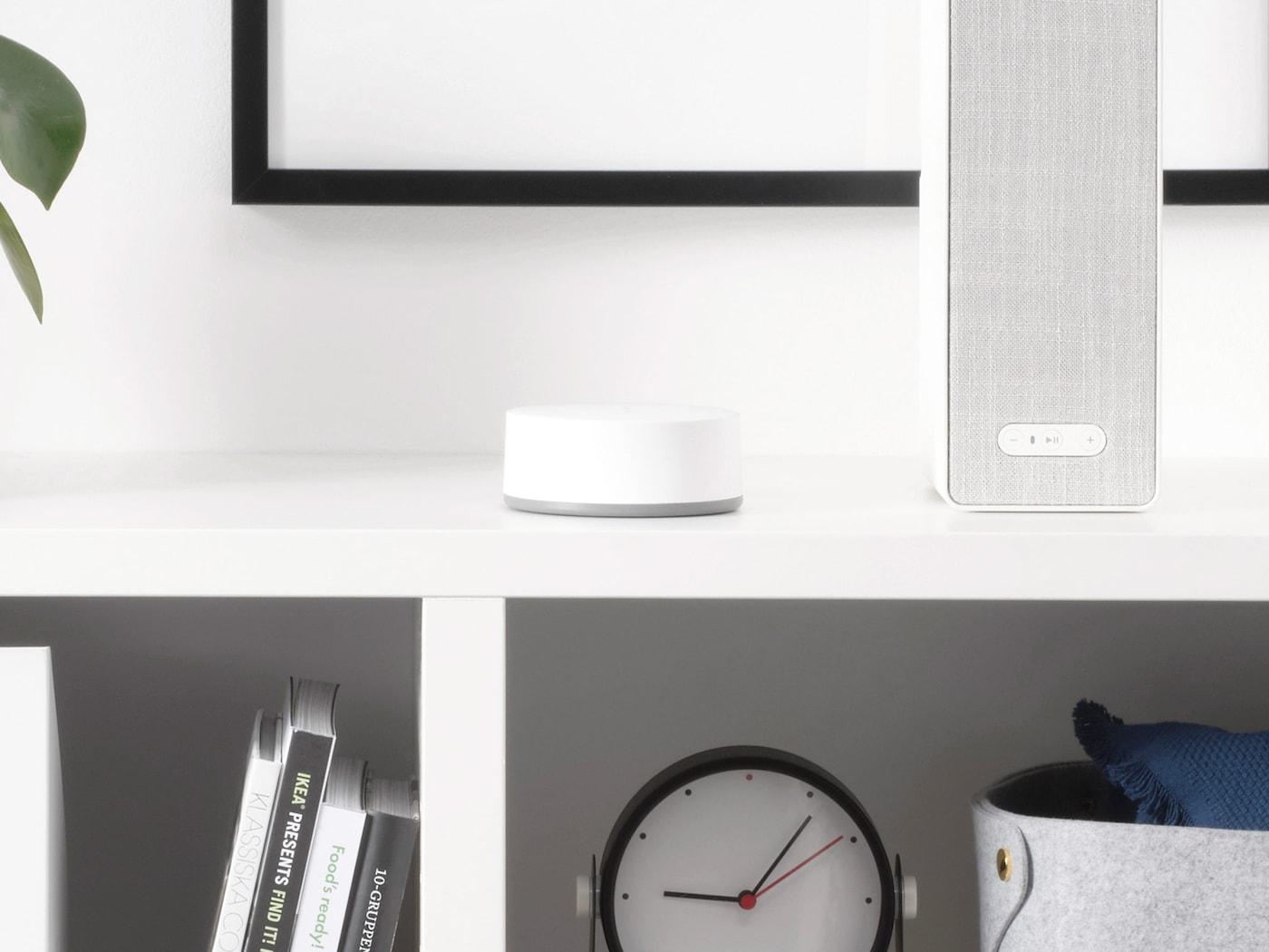 อุปกรณ์เกตเวย์ TRÅDFRI/ทรวดฟรี อยู่บนตู้หนังสือสีขาวที่ตกแต่งไว้แล้ว