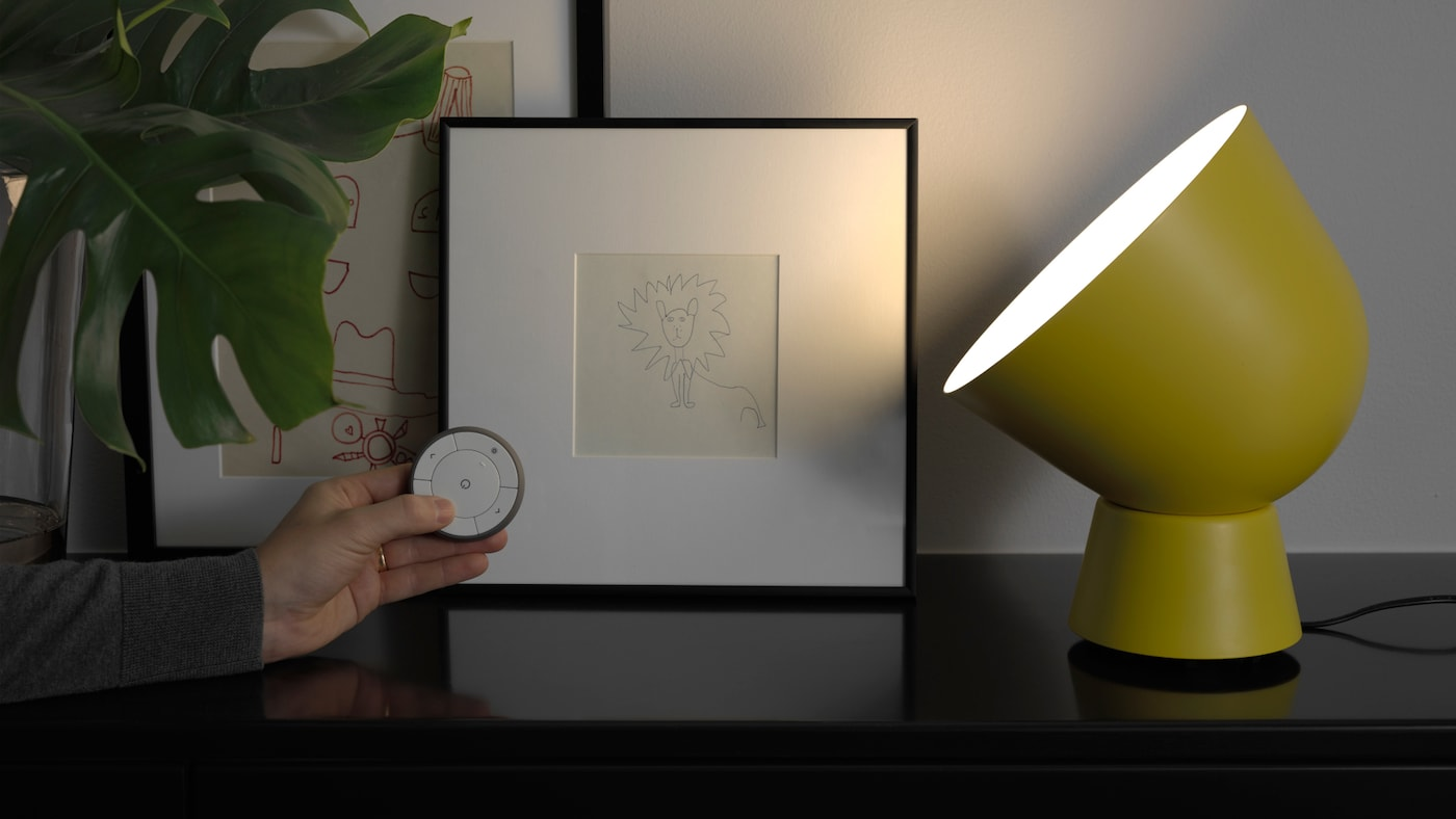 TRÅDFRI smart LED-lampa i en gul bordslampa.
