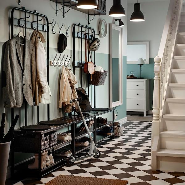 Tradicionalno predsoblje s crno-bijelim kockastim podom i dva crna stalka za kapute te klupama za odlaganje obuće postavljenim jedna pokraj druge.
