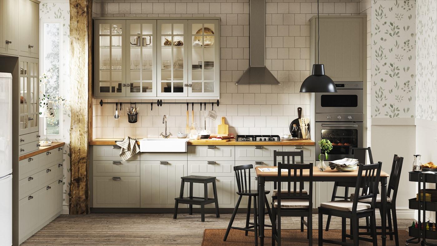 Tradisjonelt kjøkken med beige skap, hvite fliser, tregulv, blomstermønstret tapet og svart spisestuesett.